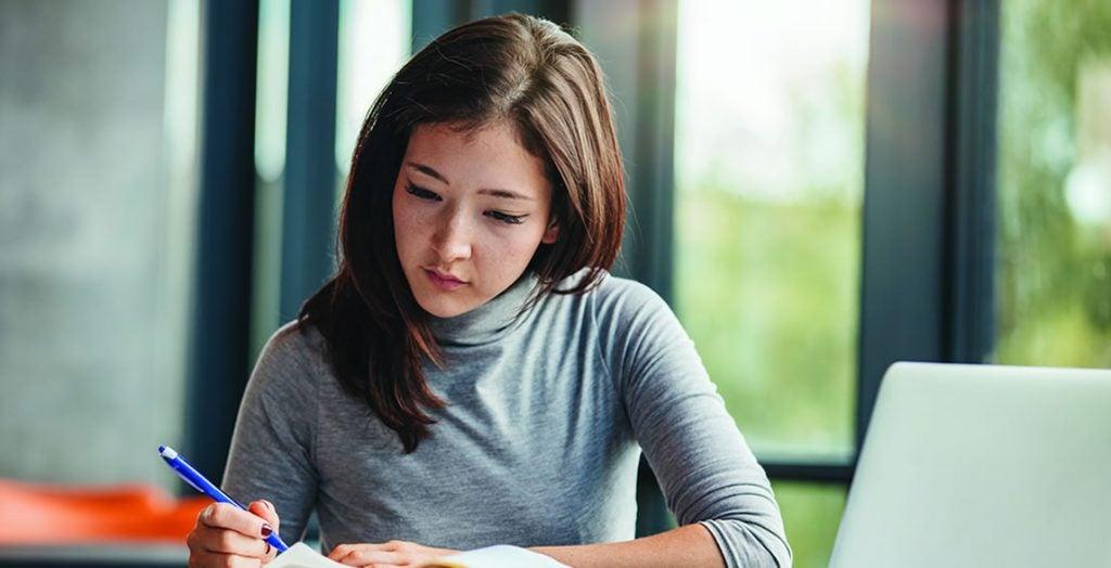 Mulher escrevendo um relatório. Benefícios do uso de contraceptivos para a pele.