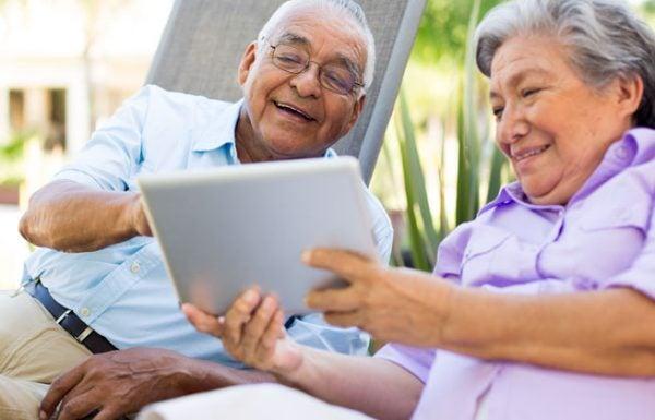 Casal idoso se entretendo em frente a um tablet: conheça nossas dicas e orientações posturais em osteoartrite