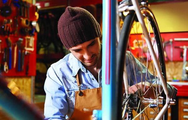 Jovem usando touca e macacão conserta roda de bicicleta em oficina de garagem