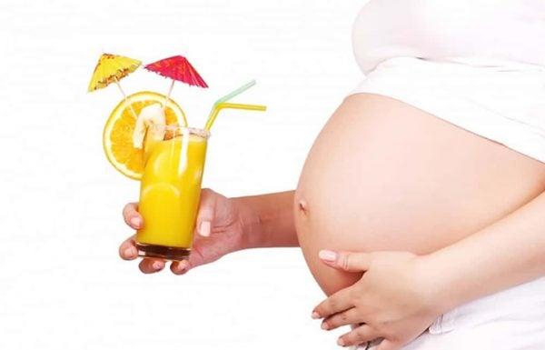 Mulher grávida segura um copo de suco de laranja: alimentação saudável é importante também no segundo trimestre de gravidez