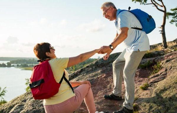Homem idoso ajuda senhora a subir em caminhada ao ar livre.