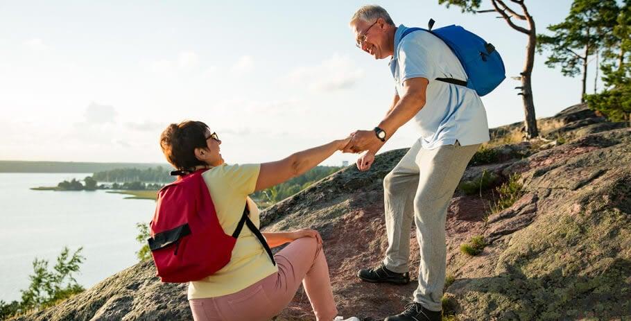 Homem idoso ajuda senhora em caminhada ao ar livre.