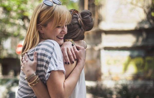 Duas mulheres sorrindo se abraçam na rua