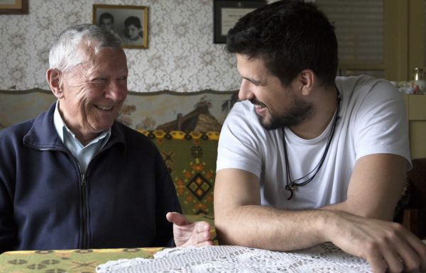 Pai e filho conversam animadamente na mesa da sala