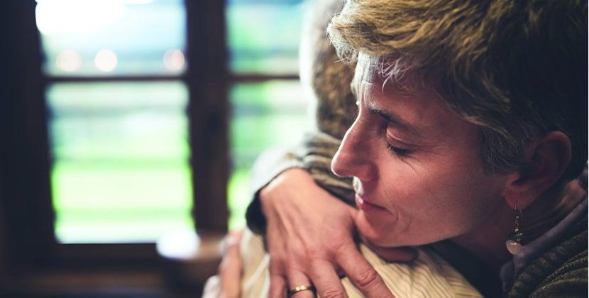 Importância de diagnosticar e tratar a depressão: apoio familiar.  Close de duas pessoas que se abraçam de forma emocionada.