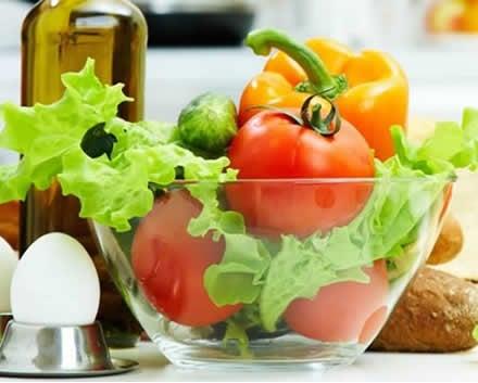 Prato de salada com tomate, alface pimentões e pepino. Azeite, pães e ovos.