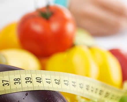 Importância de diagnosticar e tratar a depressão: alimentação saudável. Imagem de legumes e fita métrica sugerem uma dieta saudável para manutenção do peso adequado.