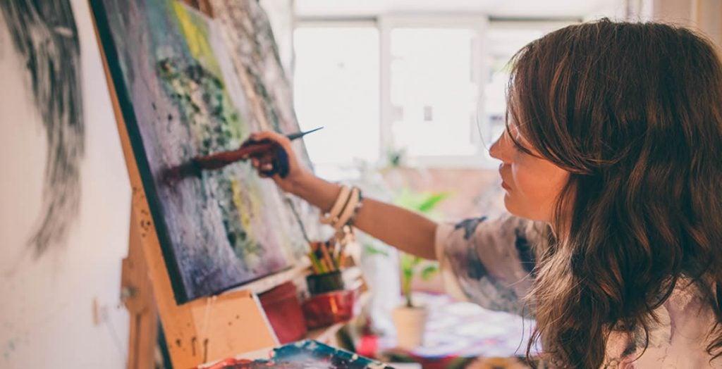 Mulher sentada em estúdio pintando uma tela a óleo.