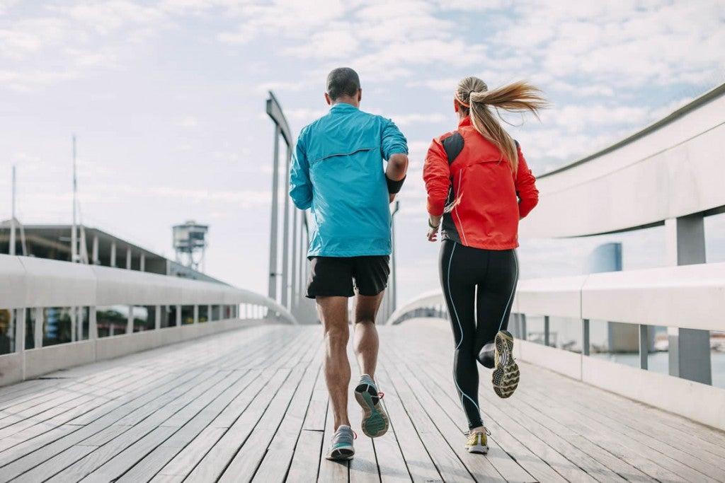 Casal correndo sobre ponte