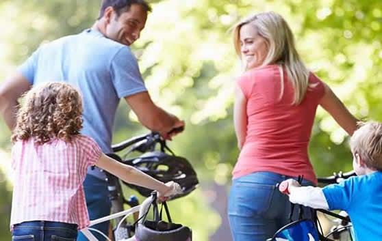 Importância de diagnosticar e tratar a depressão: atividade física. Família reunida em passeio de  bicicleta em em parque. Mãe, pai e crianças alegres e sorridentes.