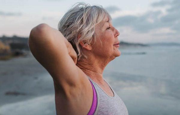 Mulher idosa fazendo exercícios na praia