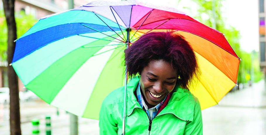Mulher com guarda-chuva colorido passeando na chuva.