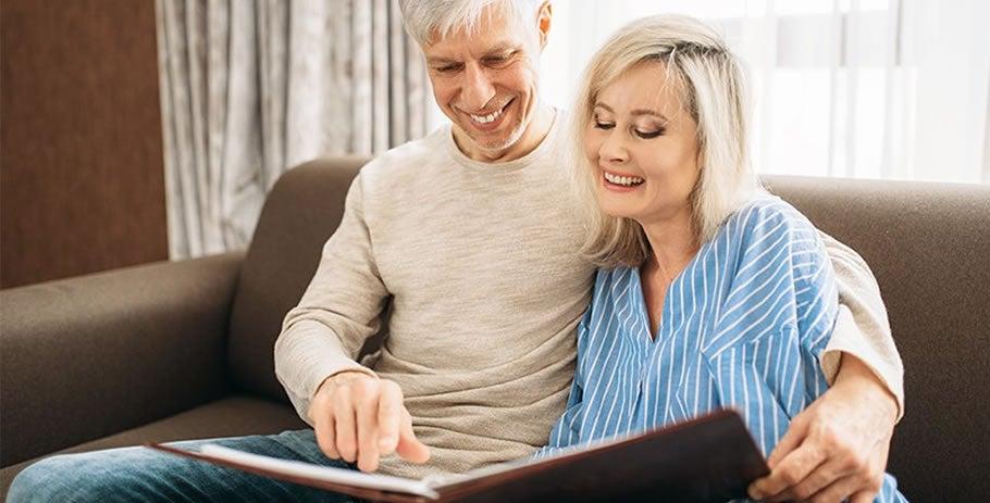 Casal maduro sentado em sofá na sala vendo álbum de fotos: conheça os mitos e verdades sobre osteoartrite