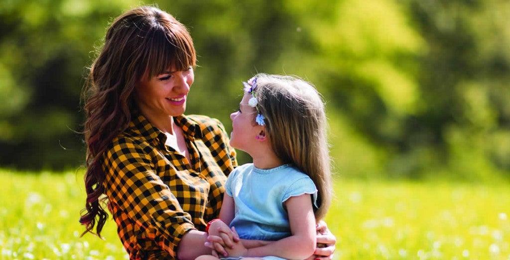 Mãe olha para filha em seu colo em um parque: a constipação atinge crianças e adultos