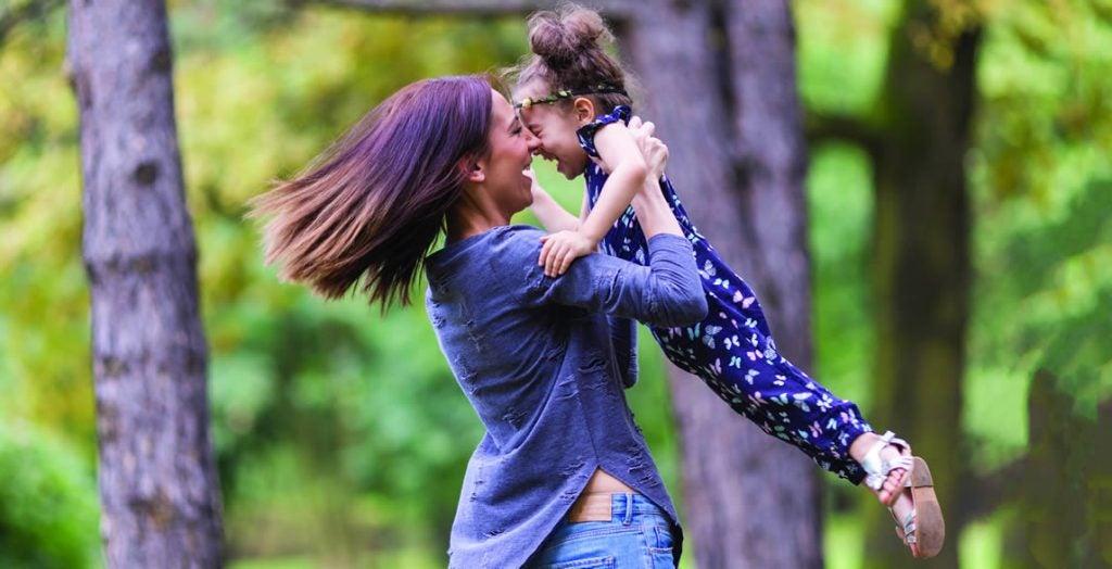 Mãe com filha no colo se divertindo em parque: qualidade de vida na SII