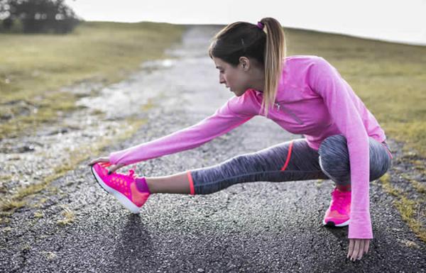 Mulher jovem fazendo alongamento antes de se exercitar
