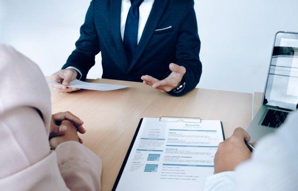 Pessoas em uma mesa de reunião com formulários