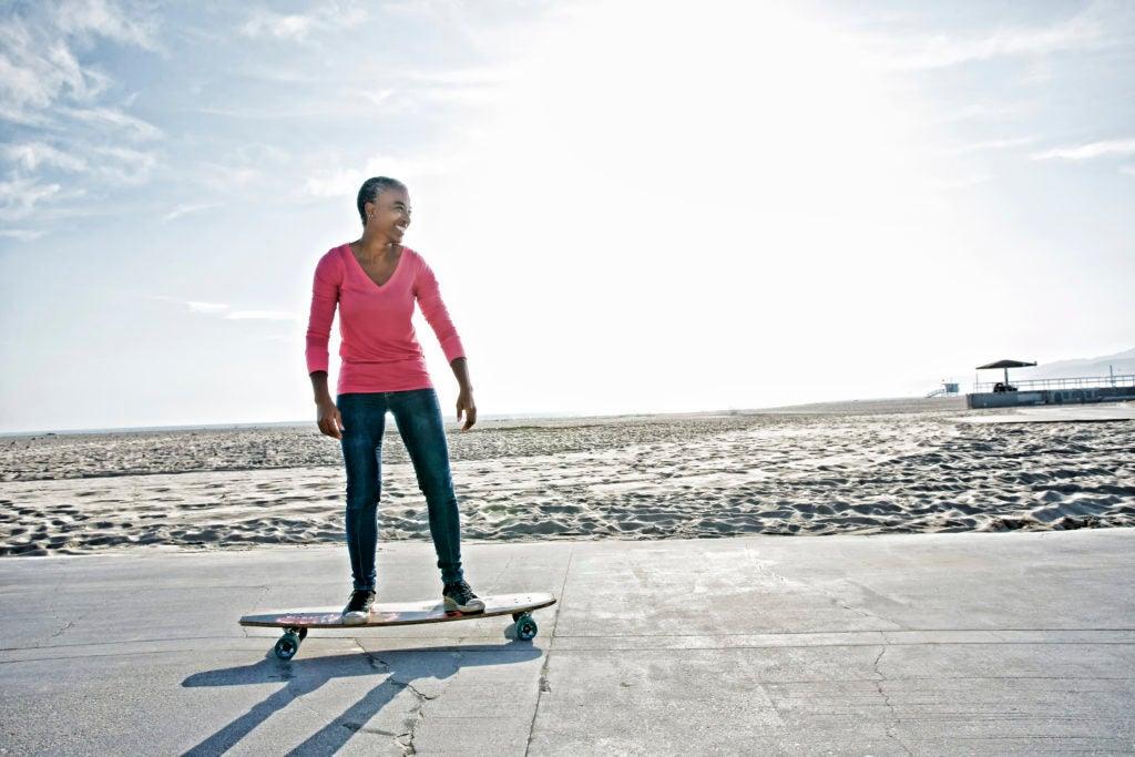 Mulher de meia idade anda de skate na praia em alusão a adotar um estilo de vida saudável no trabalho