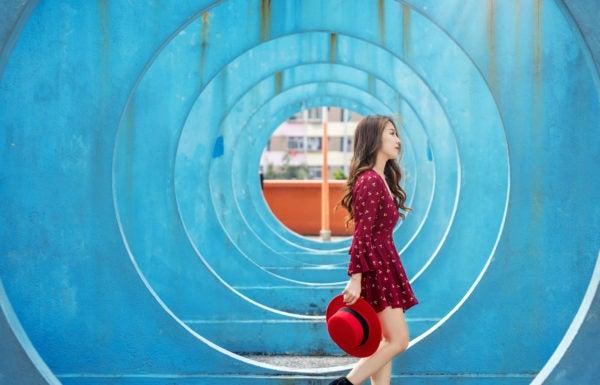 Mulher jovem segurando chapéu passeia em parque com escultura em espiral ao fundo.