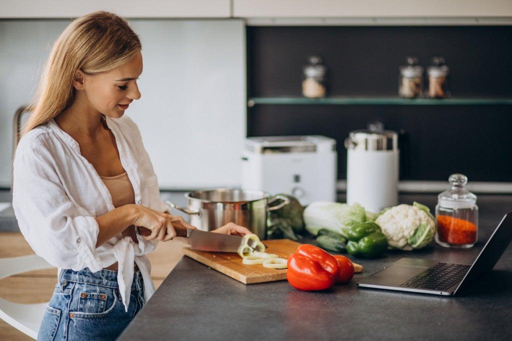 Mulher prepara refeição saudável em casa, com vegetais frescos.