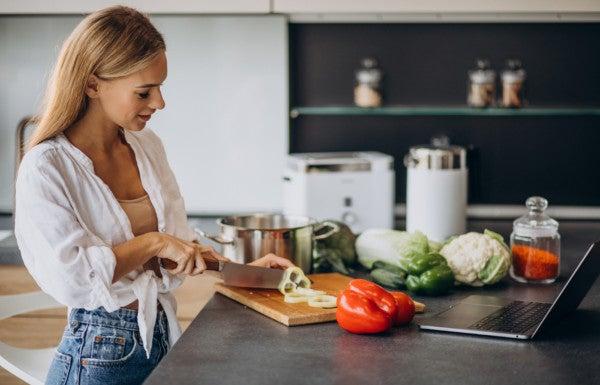 Mulher prepara refeição saudável em casa