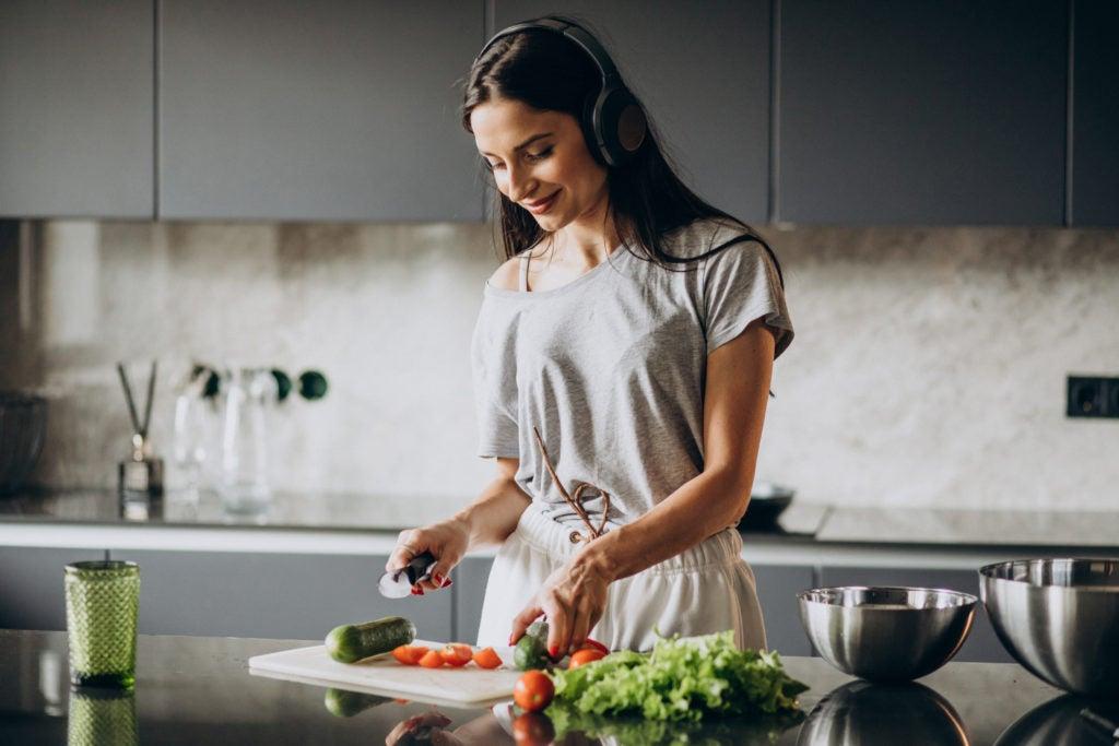 Mulher preparando refeição saudável em casa, hábito que pode minimizar o impacto dos sintomas da SII em sua vida