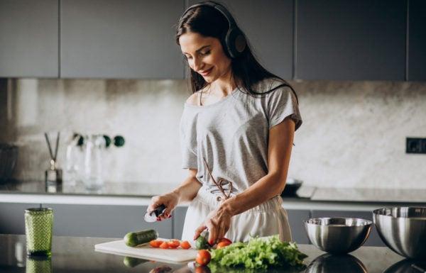 Mulher preparando refeição saudável em casa