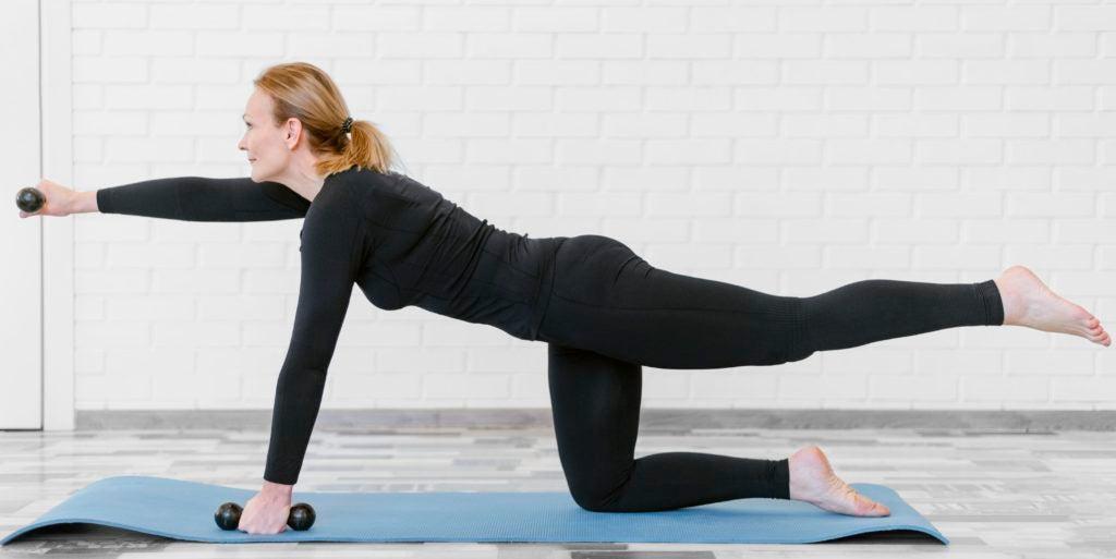 Mulher madura fazendo atividade com pesos em tapete no chão, demonstrando que cuidados com alimentação e exercícios podem ajudar a aliviar sintomas da menopausa.