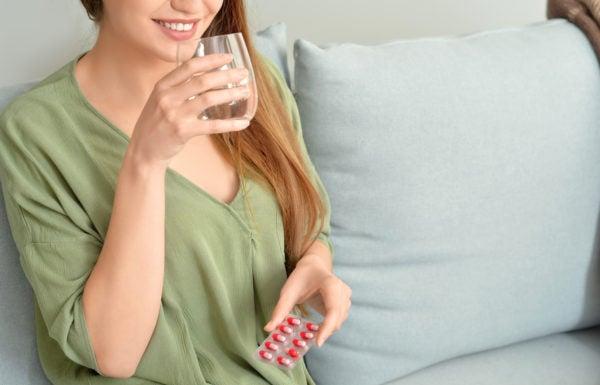 Mulher tomando medicamento para sintomas da síndrome do intestino irritável