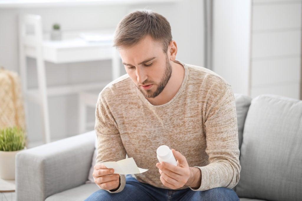 Homem lendo bula de medicamento para tratar um sintoma da síndrome do intestino irritável