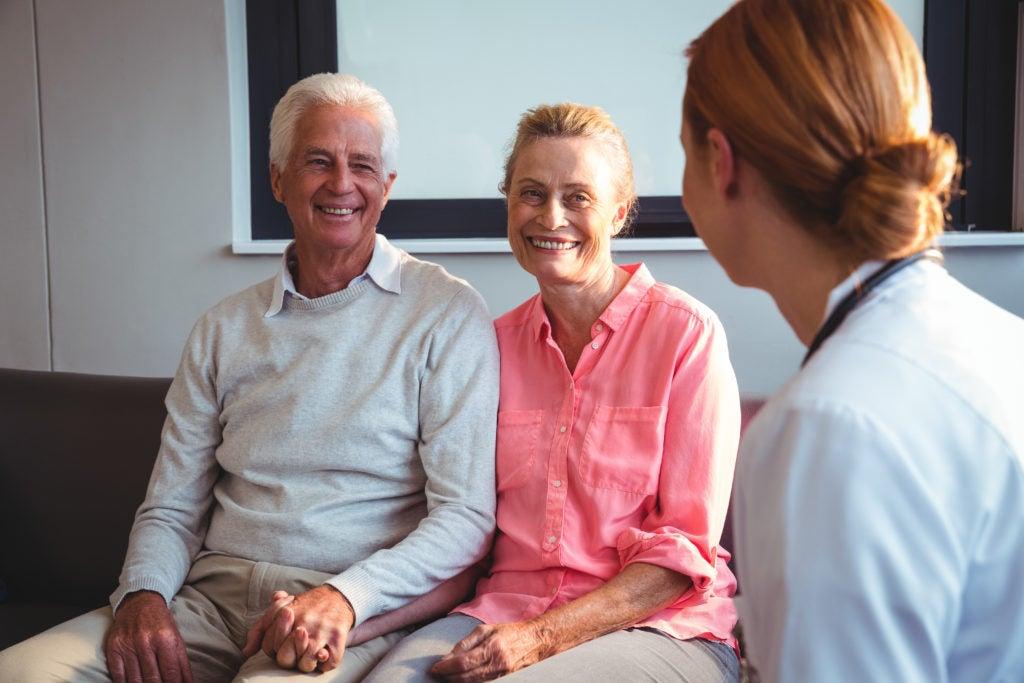 Profissional de saúde conversa com casal de meia idade, mostrando que existe tratamento para os sintomas da menopausa