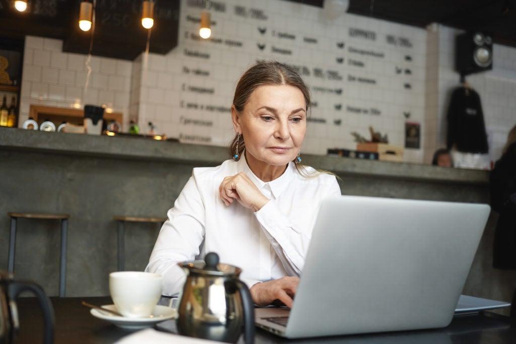 Mulher sentada em um café, pesquisando em um notebook sobre o que é menopausa
