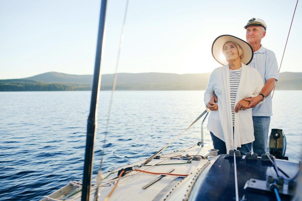Casal maduro passeia de barco em águas calmas em um dia limpo