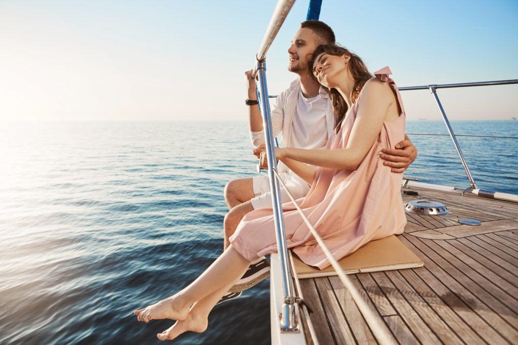 Casal abraçado em deck de barco em alto mar: a importância de aderir ao tratamento da vertigem para se sentir melhor