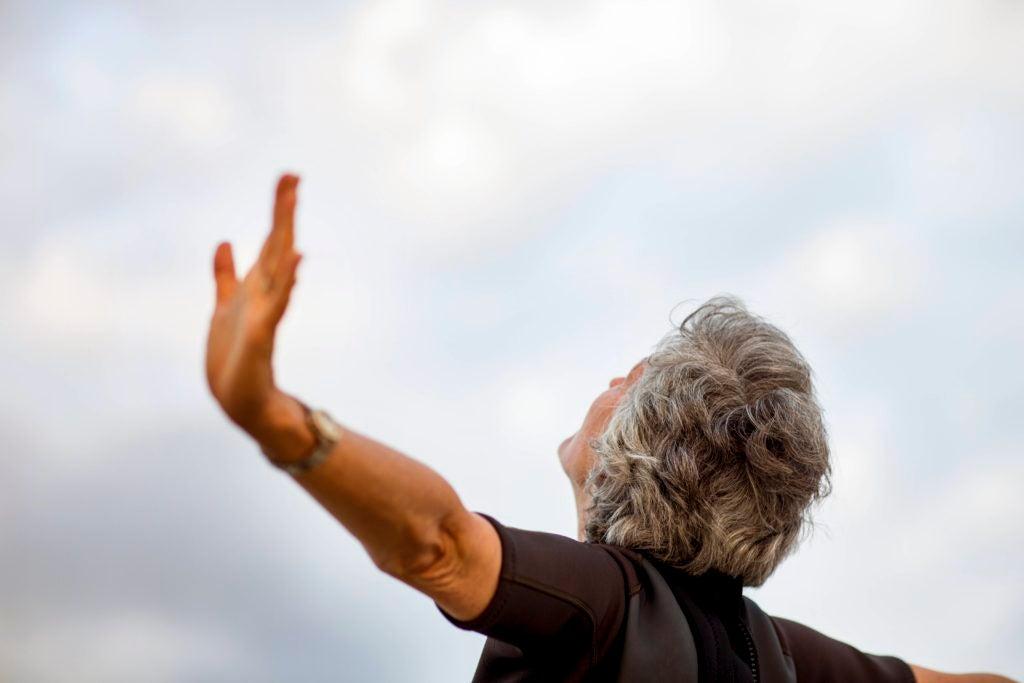 Mulher idosa de braços abertos olhando para o céu.