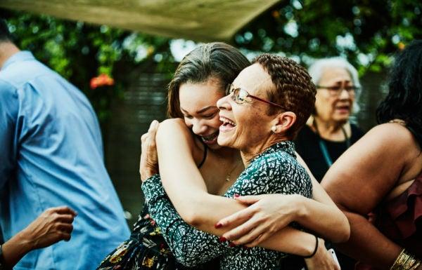 Duas mulheres se abraçam felizes em uma reunião de família.