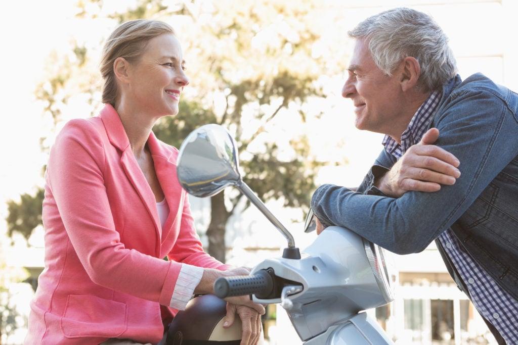 Casal de meia idade conversando em uma scooter sobre quais são os sintomas da menopausa