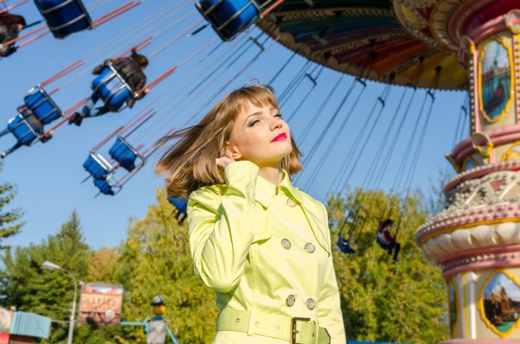 Mulher jovem vestindo casaco amarelo em frente a um carrossel em parque de diversões