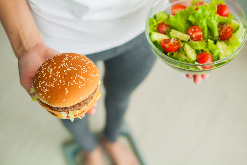 Mulher segurando sanduíche e prato de salada: nossas dicas para manejar a dieta na SII