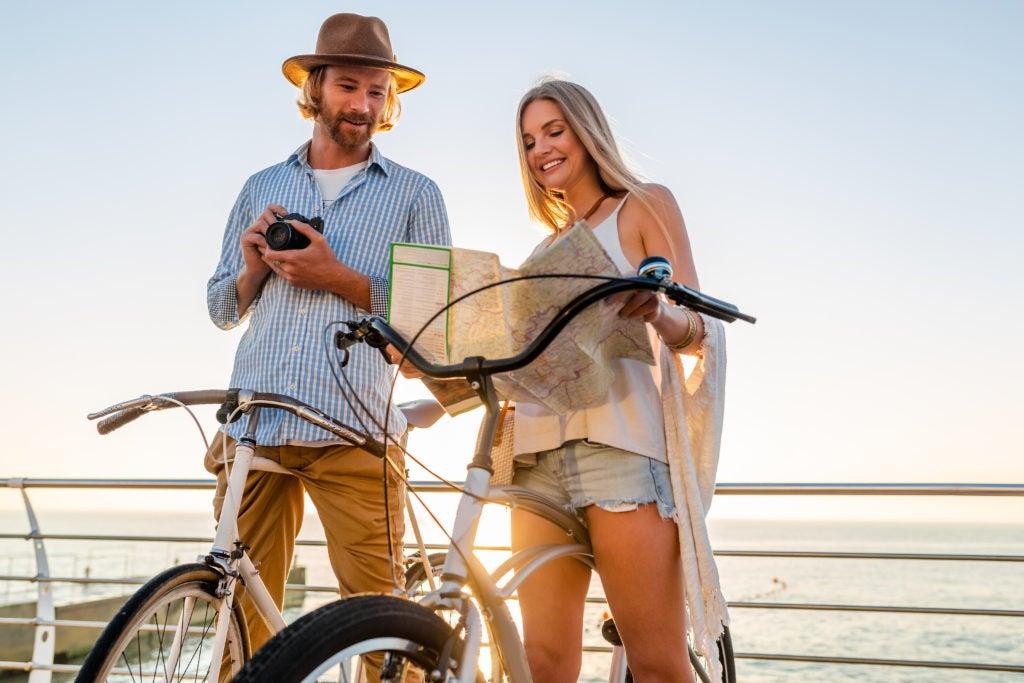 Casal consultando mapa antes de um passeio de bicicleta: é possível conviver melhor com a síndrome do intestino irritável