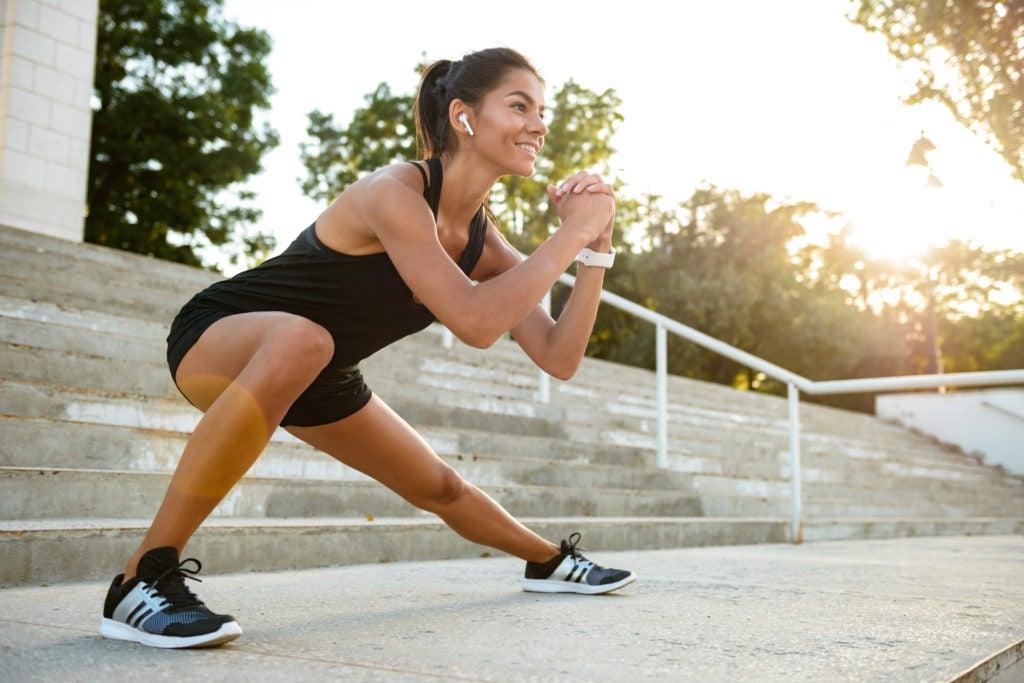 Mulher fazendo exercícios físicos com escadaria ao fundo. Mudanças gerais no estilo de vida podem melhorar seus sintomas de SII