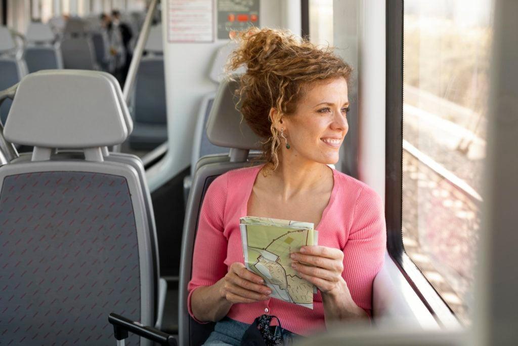 Mulher com mapa nas mãos sentada viajando de trem olha pela janela