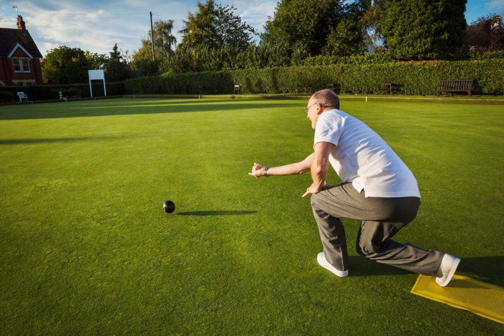 Homem de meia idade agachado em gramado fazendo lançamento de bola em jogo de bocha ou pétanque. Entender o que é colesterol é importante para cuidar melhor da saúde cardiovascular