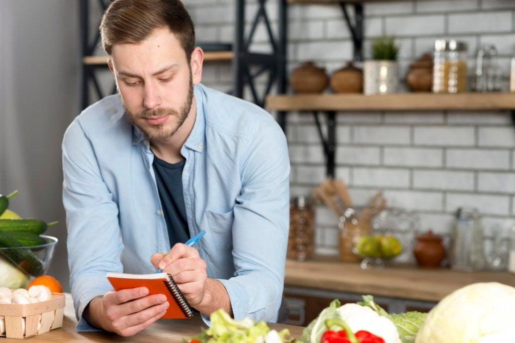 Alguns alimentos podem deflagrar crises de enxaqueca: homem jovem escrevendo uma lista de compras na cozinha, cercado de alimentos saudáveis, como vegetais
