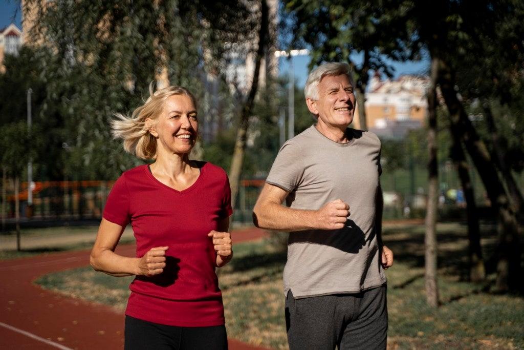 Casal maduro pratica exercícios ao ar livre, uma das atitudes simples para não transmitir ou pegar uma infecção respiratória