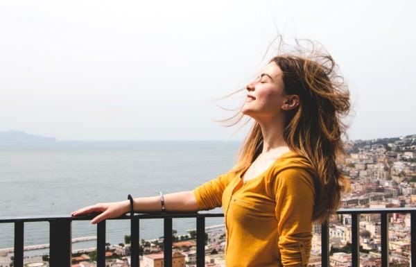 Mulher respirando profundamente com paisagem ao fundo