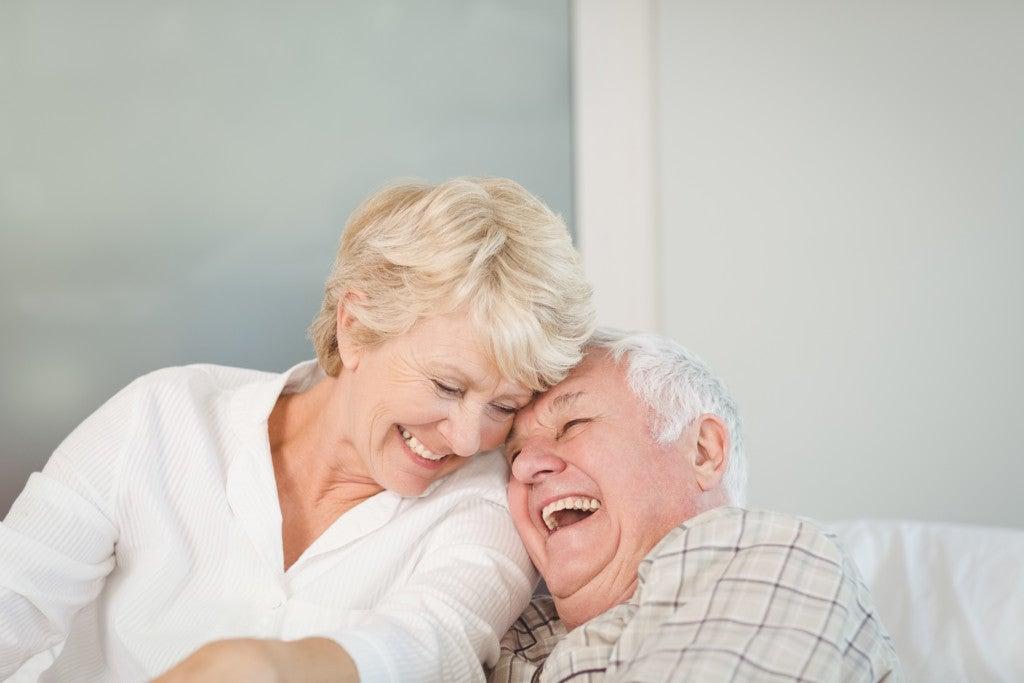 Casal de idosos dá risadas, sentados no sofá