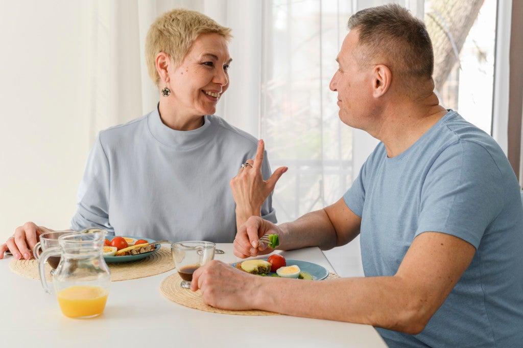 Algumas pessoas estão mais vulneráveis a infecções respiratórias. Casal maduro conversa enquanto toma o café da manhã