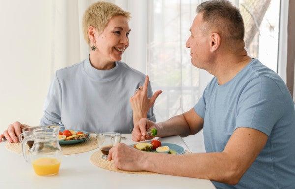 Casal maduro conversa enquanto toma o café da manhã