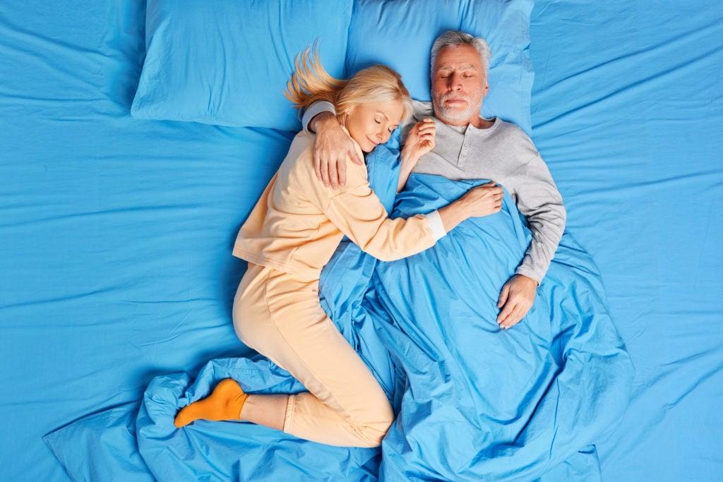 Casal de meia idade dorme tranquilamente em cama com lençois azuis. Problemas de sono são comuns em mulheres na menopausa .